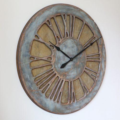 Die bemerkenswerteste 100 cm extragroße Wanduhr mit römischen Ziffern von der linken Seite aus gesehen. Die Uhr verfügt über große blaue und graue rustikal wirkende Ziffern auf einem altgoldenen Hintergrund.